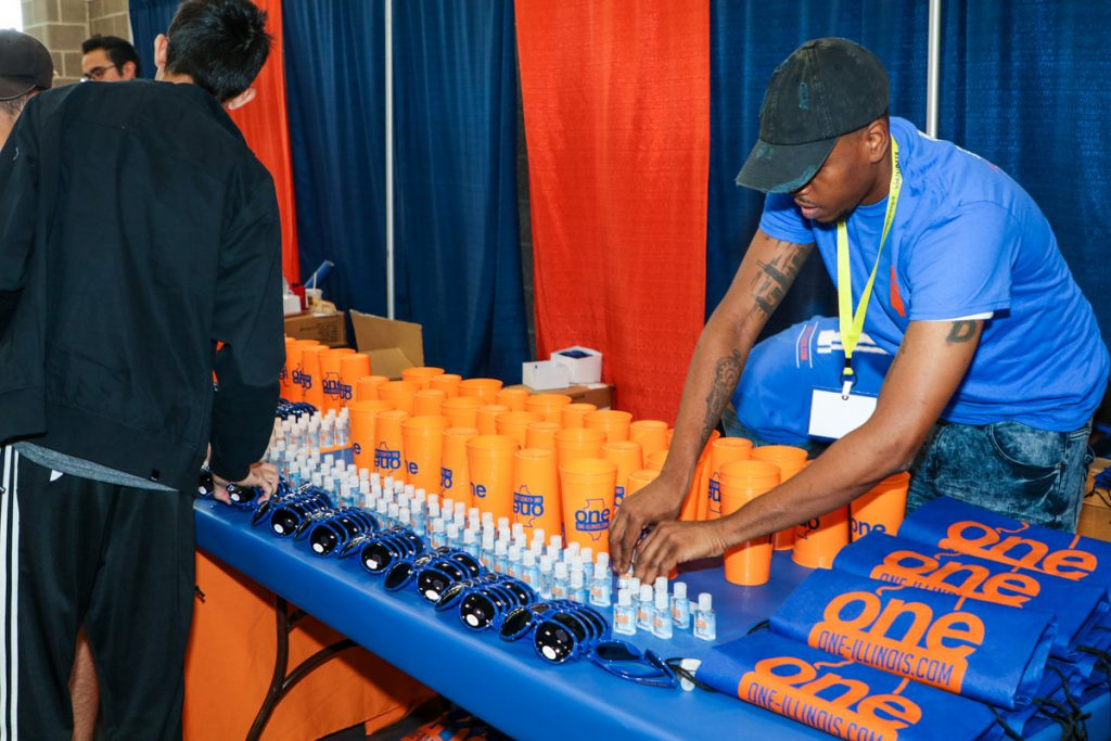 A representative at the One booth laying out free swag for the students at the 2017 Illini Fenzy.