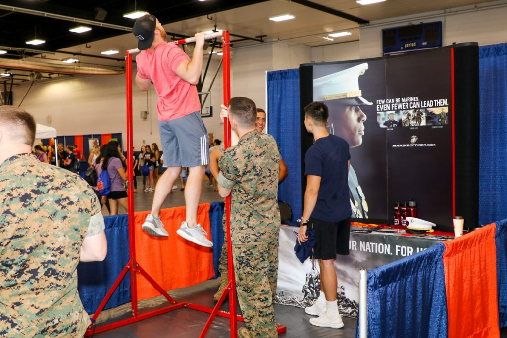 A student doing pull-ups at the US Marines' booth at the 2017 Illini Frenzy.