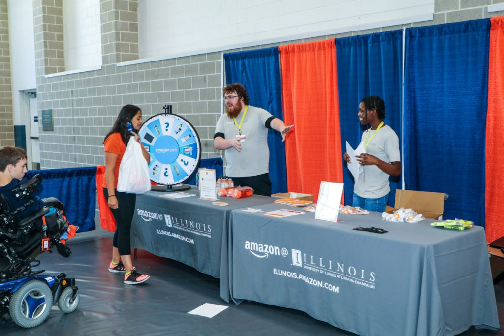 Student talks to representatives at the Amazon @ Illinois booth at the 2017 Illini Frenzy.