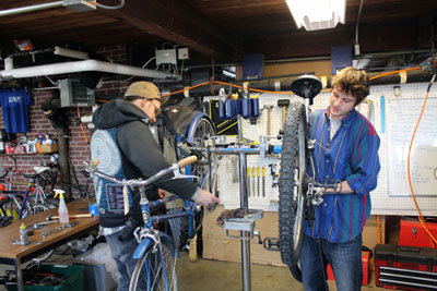 Two employees at the Campus Bike Center working on bikes.