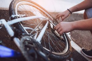 Teenager boy repair tire on bicycle summer outdoor photo, close up