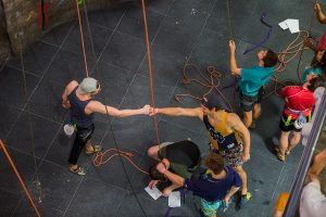 Students fist bumping on the floor at Rock Climbing event.