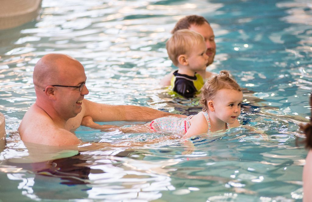 Parents and their children at a Learn-to-Swim lesson