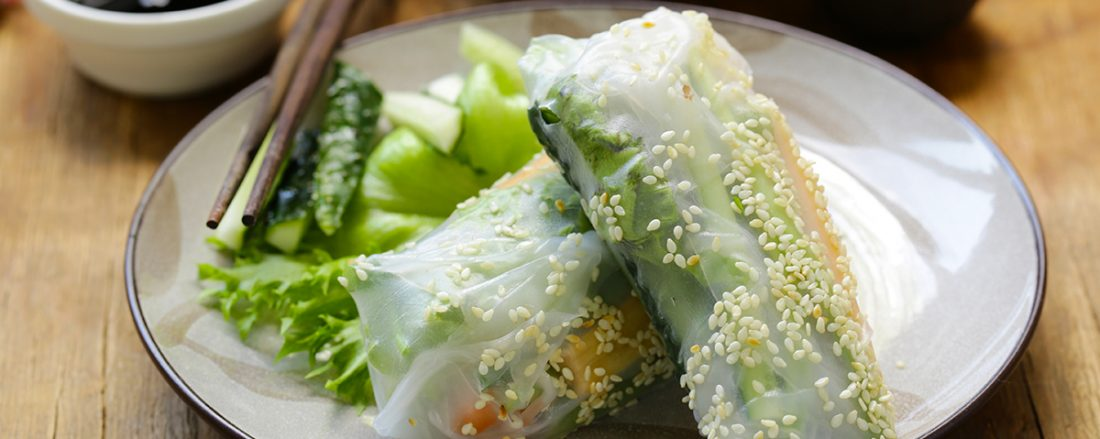 A photo of spring rolls with vegetables and fish.